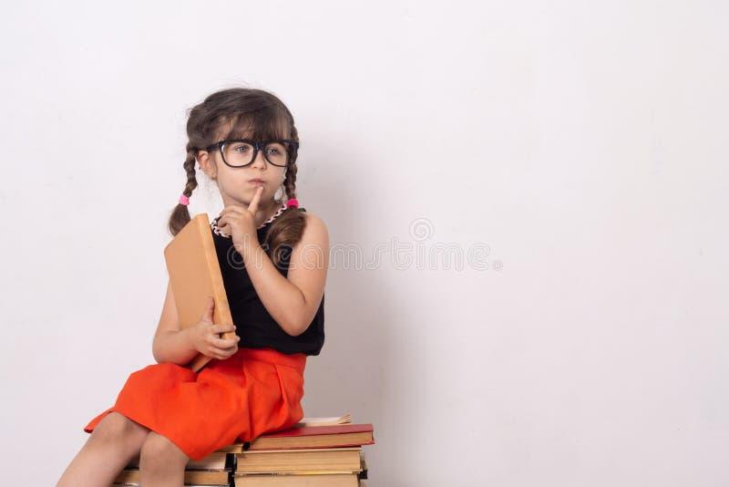 Livro de leitura bonito da menina que senta-se na pilha dos livros foto de stock