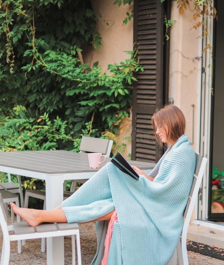 Livro de leitura bonito da moça com o copo da parte externa do chá no jardim do outono envolvido na cobertura feita malha morna imagem de stock royalty free