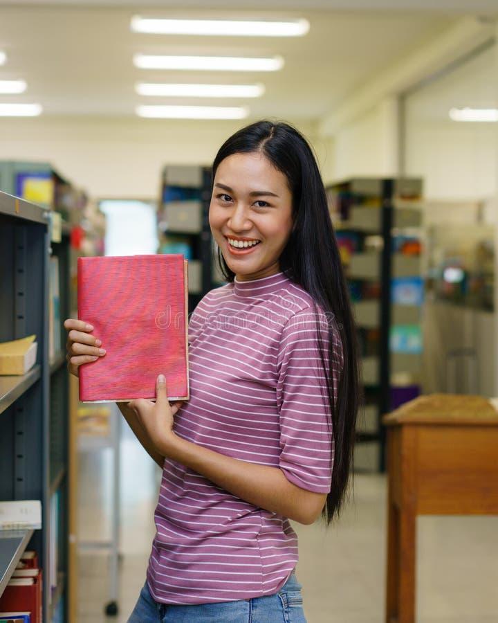Livro de leitura bonito da mulher na biblioteca foto de stock
