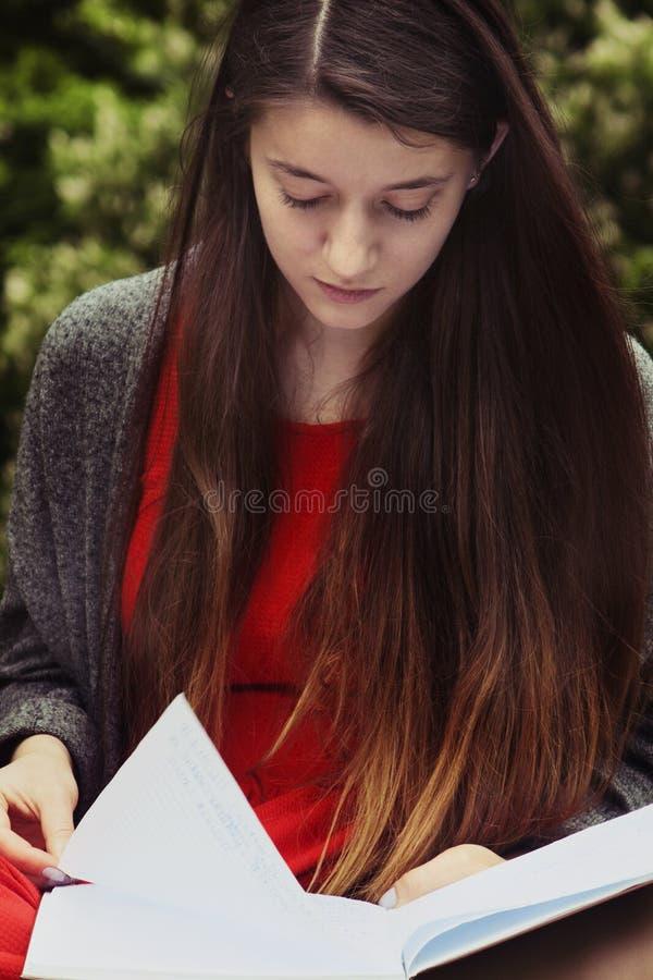 Livro de leitura bonito da mulher na natureza Estudante atrativo novo foto de stock