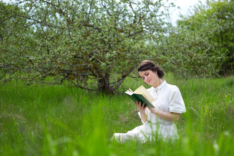 Livro de leitura bonito da mulher no prado do verão fotografia de stock