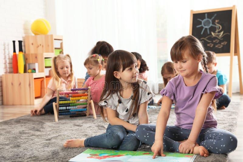 Livro de leitura bonito das meninas no assoalho quando outras crianças que jogam junto fotografia de stock