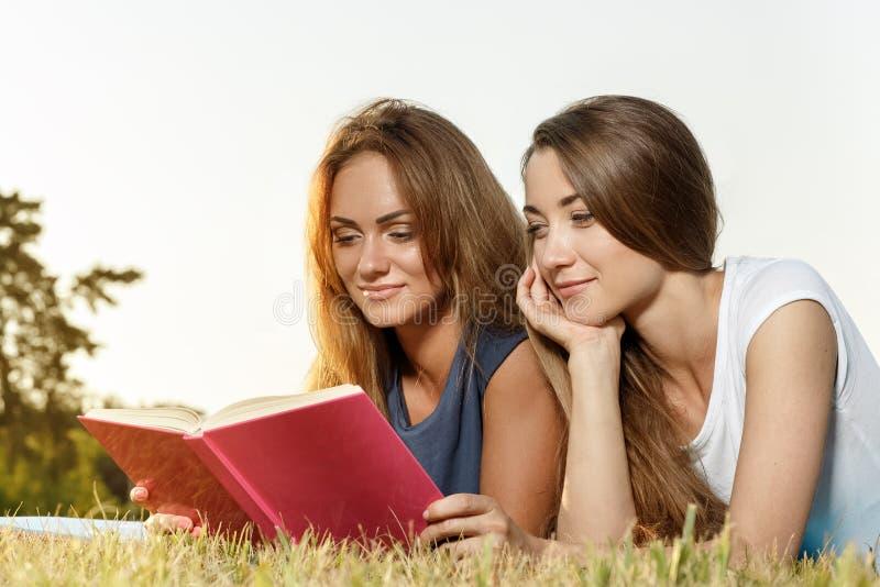 Livro de leitura bonito de duas meninas no parque foto de stock royalty free