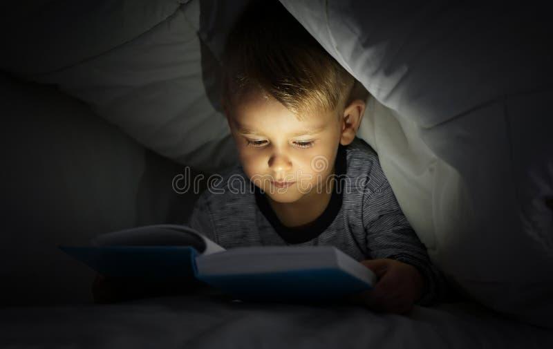 Livro de leitura bonito do rapaz pequeno na cama sob a cobertura imagem de stock royalty free