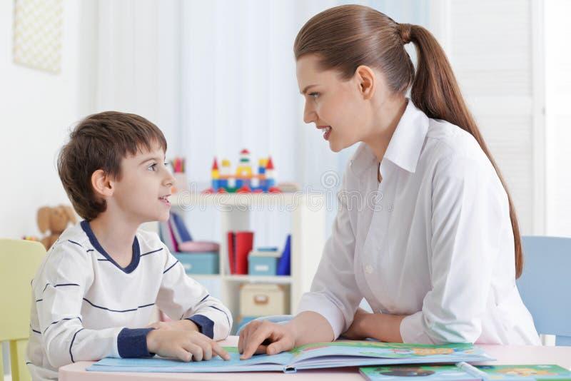 Livro de leitura bonito do rapaz pequeno no terapeuta de discurso foto de stock royalty free