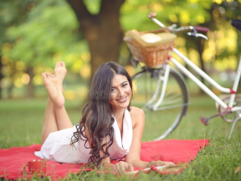 Livro de leitura bonito novo da mulher fora no parque em um dia ensolarado imagem de stock royalty free