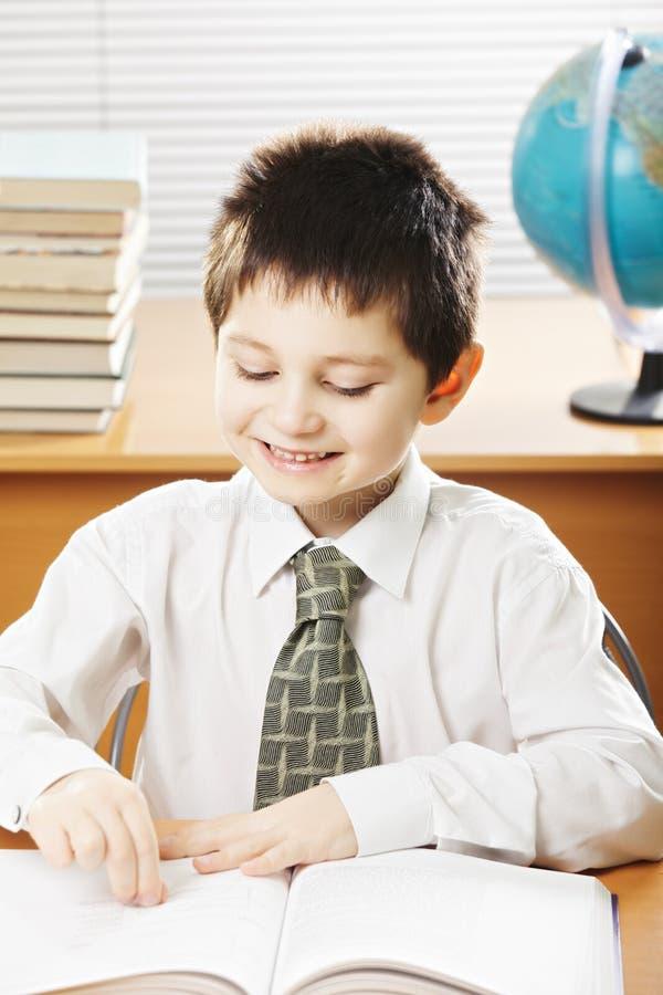 Livro de leitura caucasiano de sorriso do menino imagem de stock
