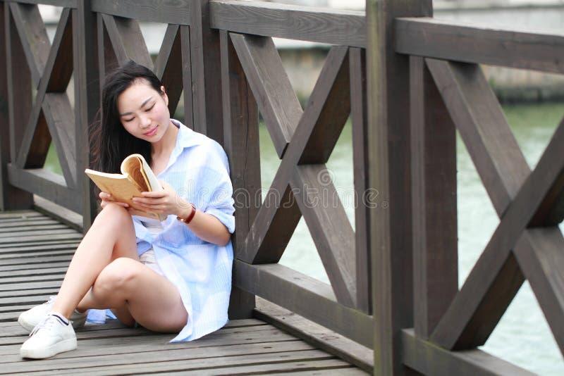 Livro de leitura chinês da menina Jovem mulher bonita loura com suporte de livro perto da cerca fotografia de stock royalty free