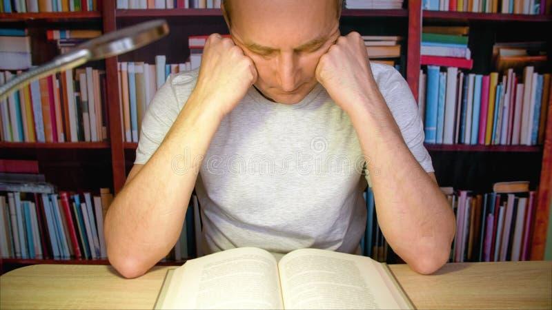 Livro de leitura concentrado do homem na tabela com a lâmpada na biblioteca acolhedor na noite fotos de stock royalty free