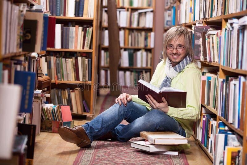 Livro de leitura considerável do homem ao sentar-se no assoalho na biblioteca foto de stock royalty free