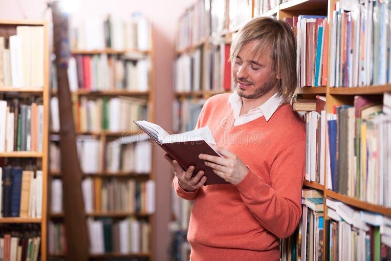 Livro de leitura considerável do homem na biblioteca fotografia de stock royalty free