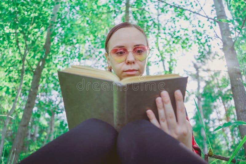 Livro de leitura considerável novo da mulher no espaço aberto imagem de stock