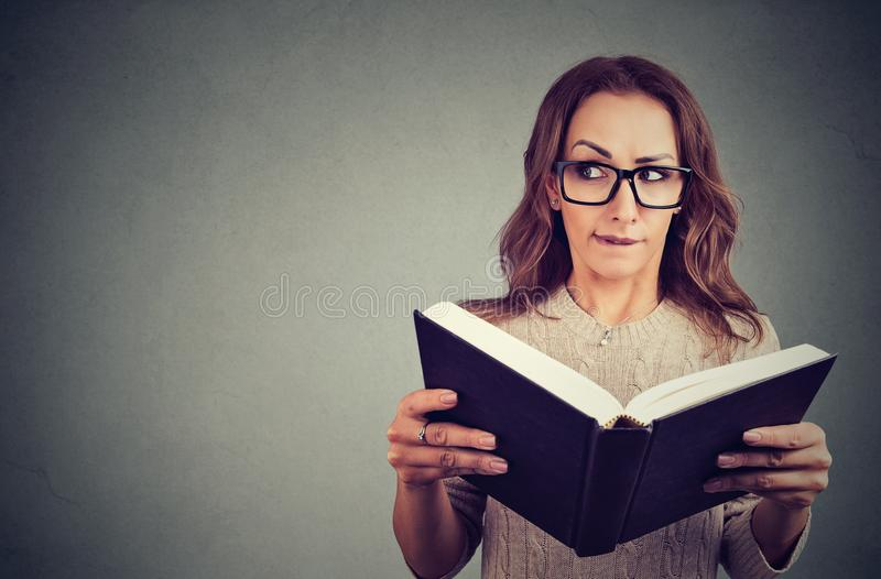 Livro de leitura curioso da mulher do lerdo imagem de stock