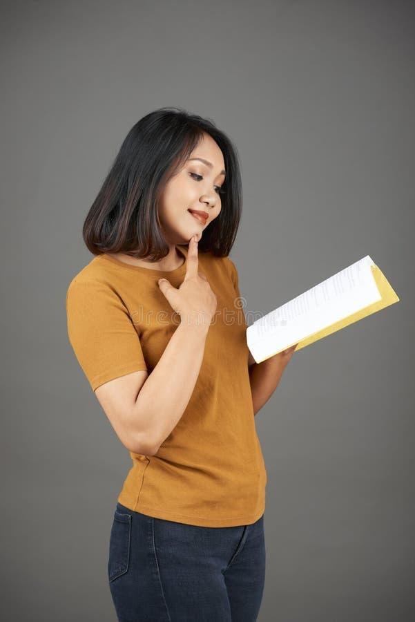 Livro de leitura curioso da mulher fotos de stock royalty free
