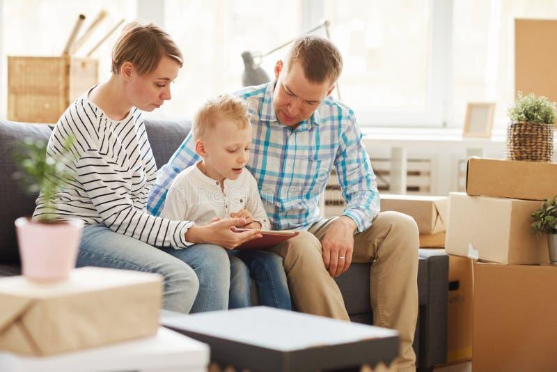 Livro de leitura curioso do filho na tabuleta com pais imagens de stock royalty free