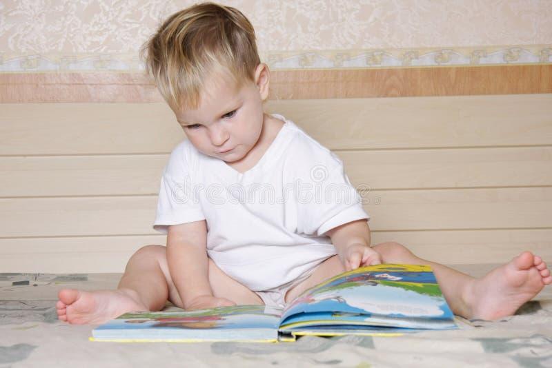 Livro de leitura da criança na cama do pai fotos de stock royalty free