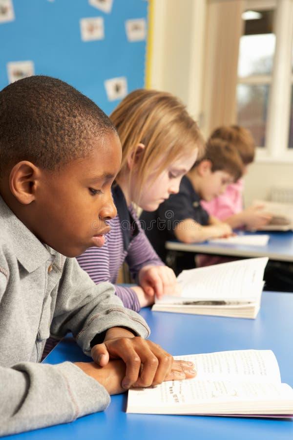 Livro de leitura da estudante na sala de aula imagem de stock