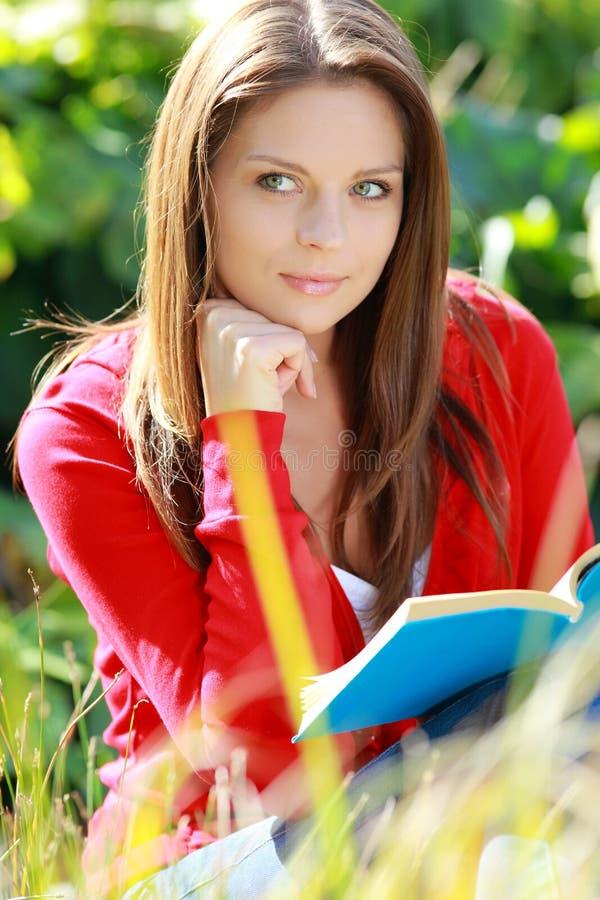 Livro de leitura da estudante no parque do outono. fotografia de stock royalty free