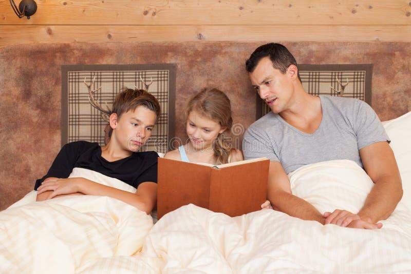 Livro de leitura da filha ao irmão e ao pai - família feliz fotos de stock