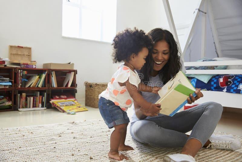 Livro de leitura da filha da mãe e do bebê na sala de jogos junto imagens de stock royalty free