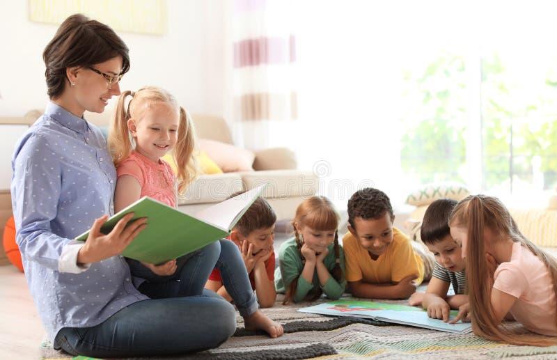 Livro de leitura da jovem mulher às crianças pequenas dentro imagem de stock