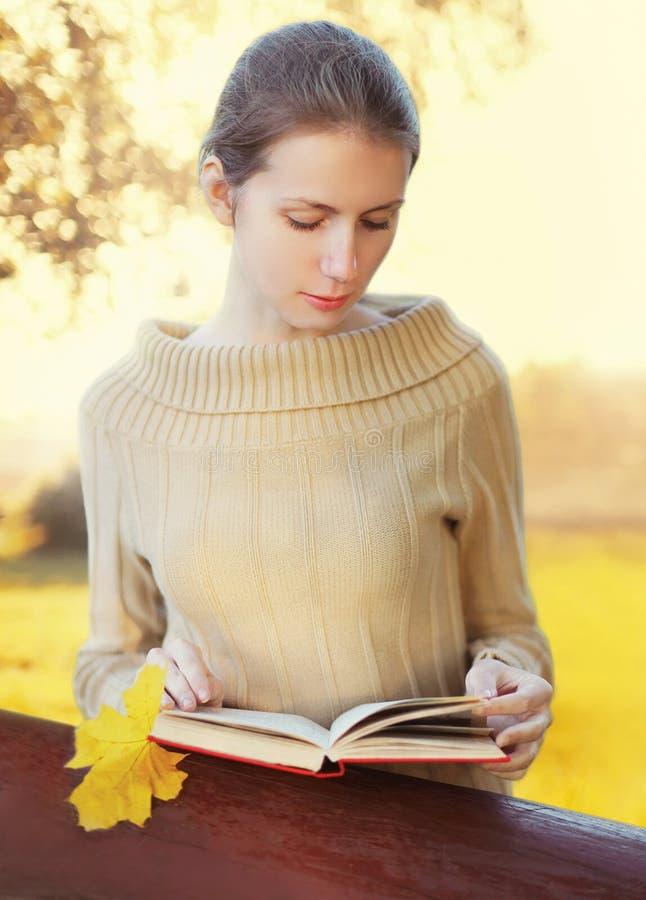 Livro de leitura da jovem mulher do retrato no outono ensolarado fotografia de stock royalty free