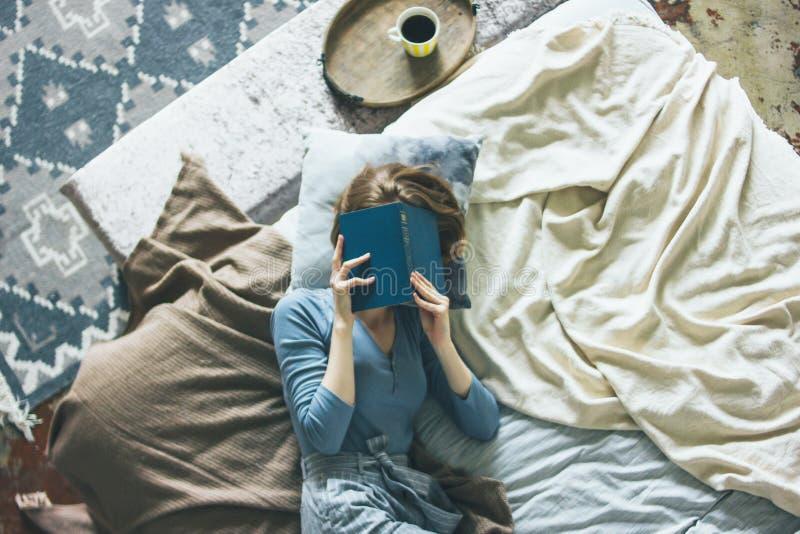 Livro de leitura da jovem mulher na cama na sala do sótão, vida lenta imagens de stock
