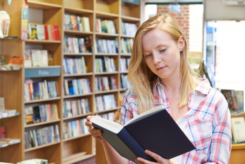 Livro de leitura da jovem mulher na livraria imagem de stock