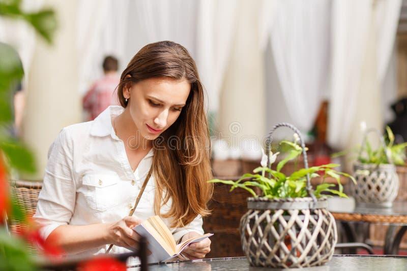 Livro de leitura da jovem mulher na tabela no café fotos de stock royalty free