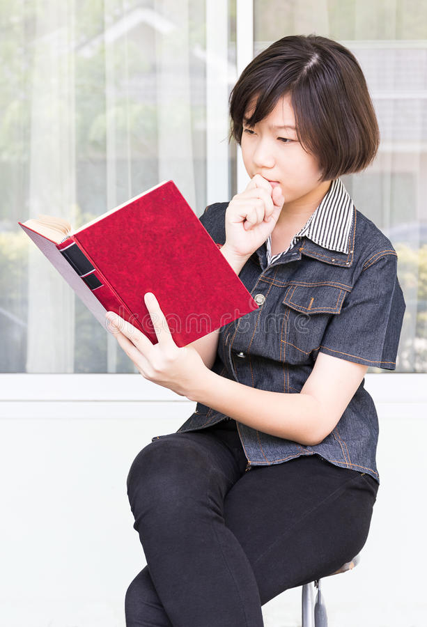 Livro de leitura da jovem mulher que senta-se na cadeira foto de stock