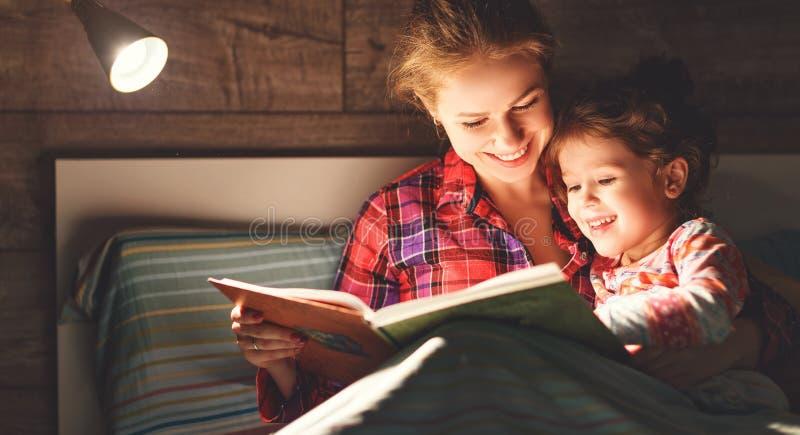 Livro de leitura da mãe e da criança na cama antes de ir dormir imagens de stock