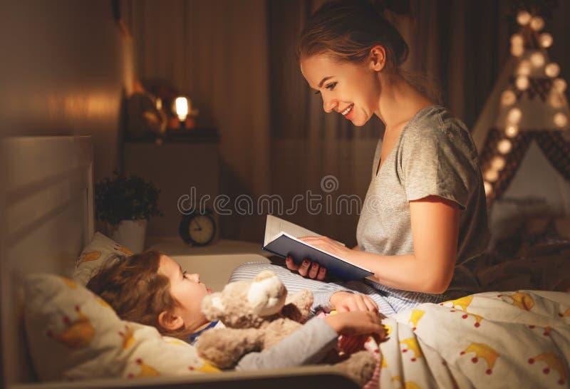 Livro de leitura da mãe e da criança na cama antes de ir dormir imagem de stock royalty free