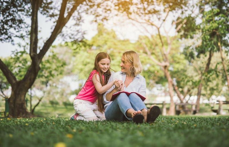 Livro de leitura da mamã e da filha no parque imagens de stock royalty free