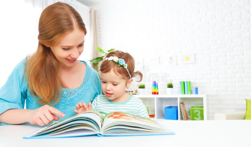 Livro de leitura da matriz e da criança em casa foto de stock
