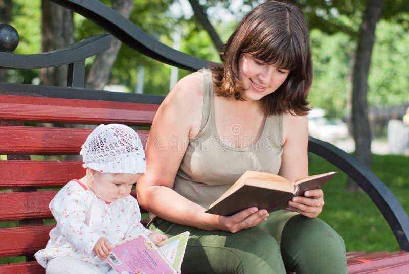 Livro de leitura da matriz e da filha fotos de stock