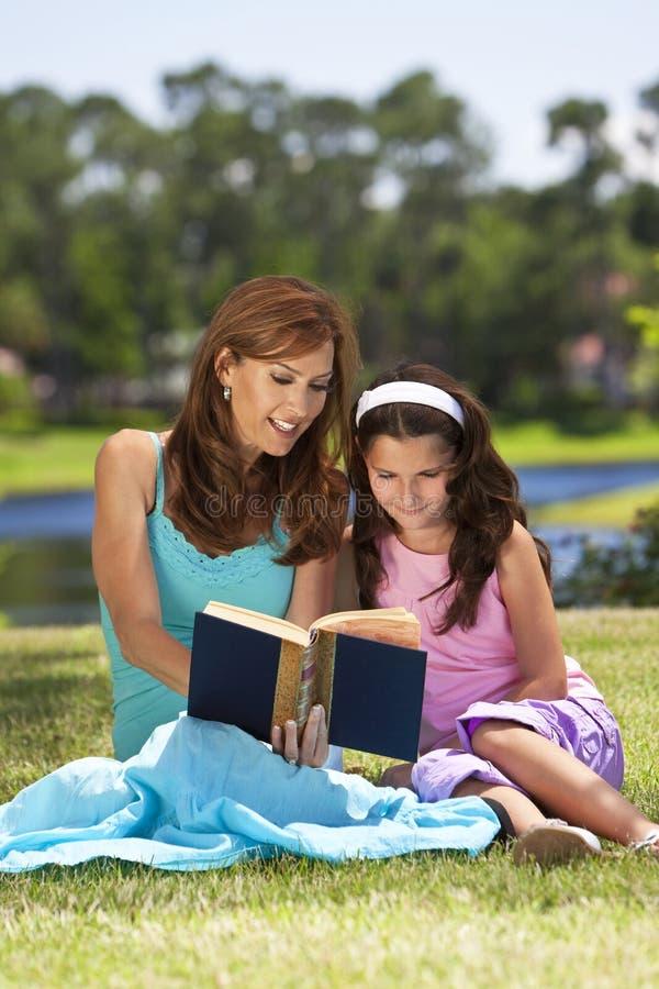 Livro de leitura da matriz e da filha junto fora imagens de stock royalty free