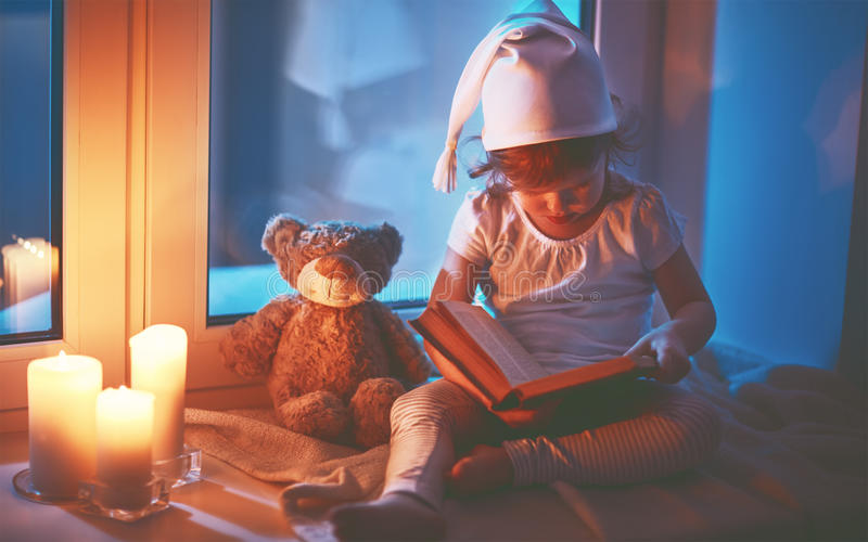 Livro de leitura da menina da criança pequena pela janela antes das horas de dormir foto de stock