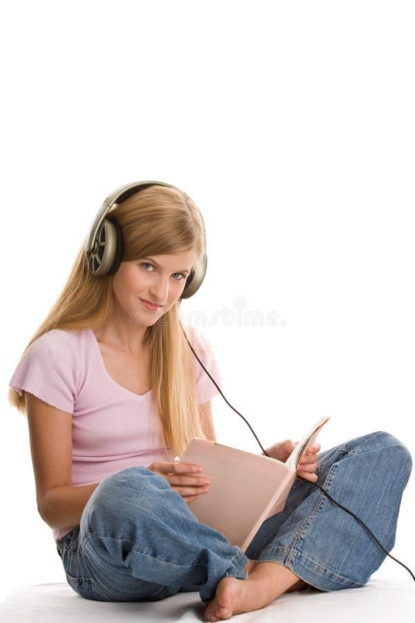 Livro de leitura da menina e escuta a música imagem de stock
