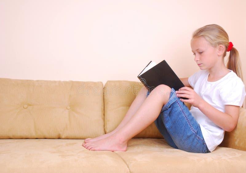 Livro de leitura da menina no sofá fotografia de stock