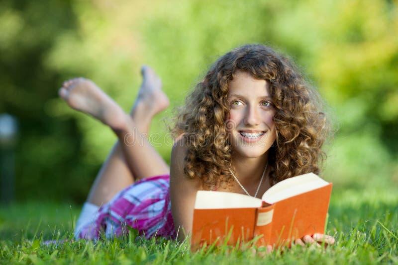 Livro de leitura da moça ao encontrar-se na grama fotos de stock