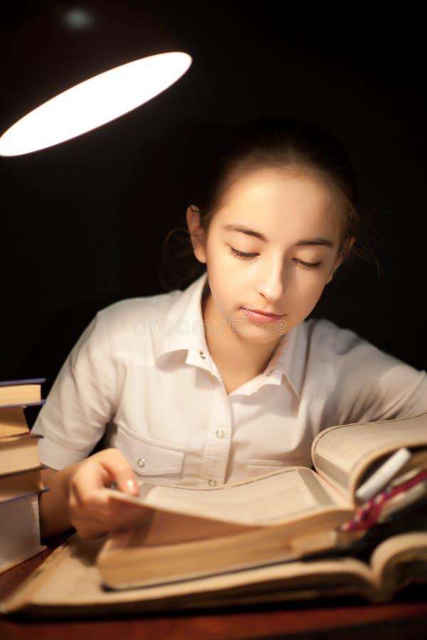 Livro de leitura da moça na obscuridade da noite na biblioteca fotos de stock royalty free