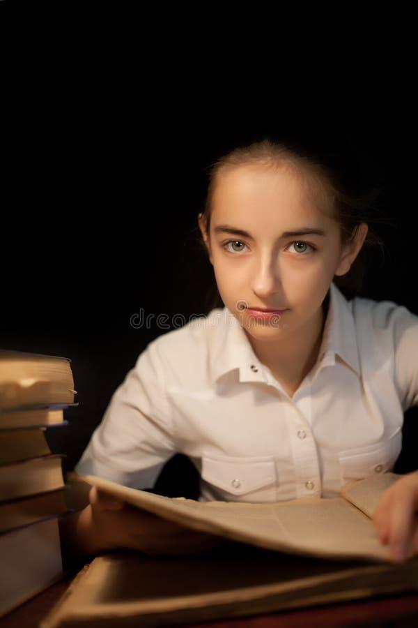 Livro de leitura da moça na obscuridade da noite na biblioteca imagens de stock royalty free