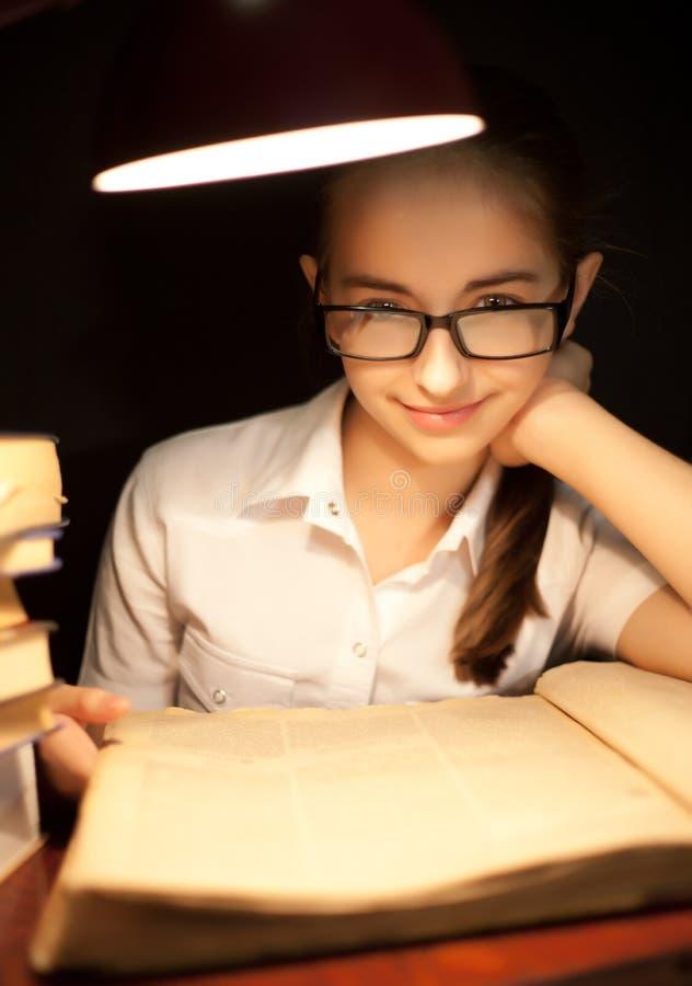 Livro de leitura da moça sob a lâmpada fotografia de stock