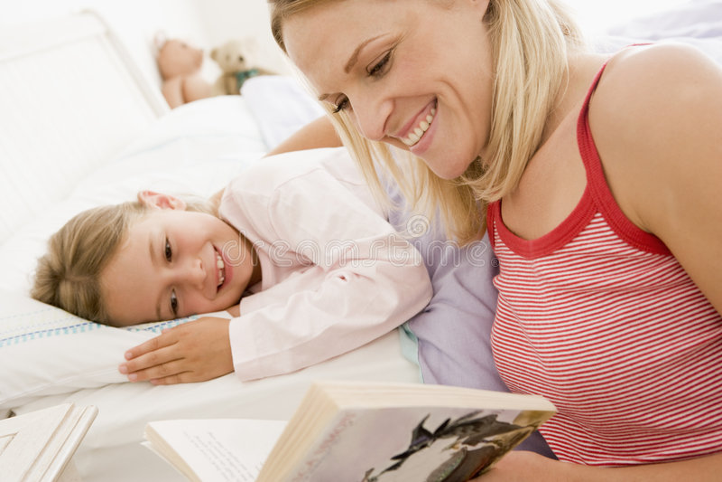 Livro de leitura da mulher à rapariga no sorriso da cama fotografia de stock royalty free