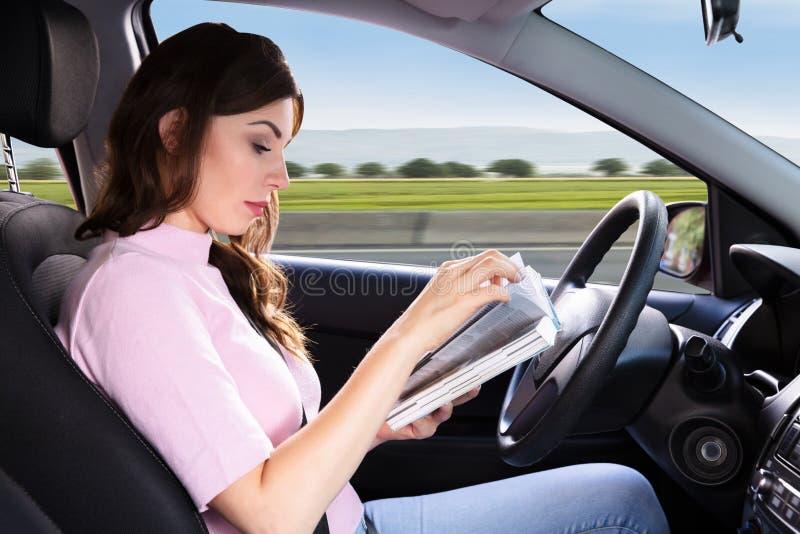 Livro de leitura da mulher ao conduzir o carro fotografia de stock