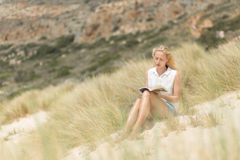 Livro de leitura da mulher, apreciando o sol na praia fotos de stock