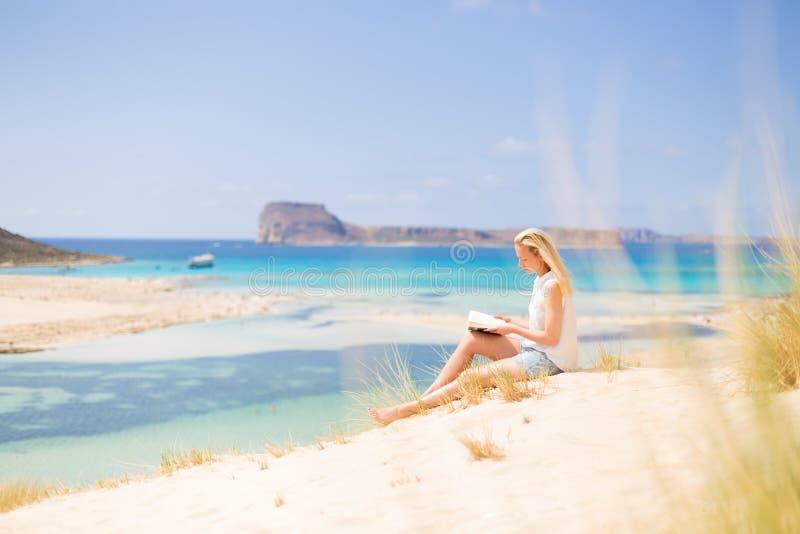 Livro de leitura da mulher, apreciando o sol na praia foto de stock