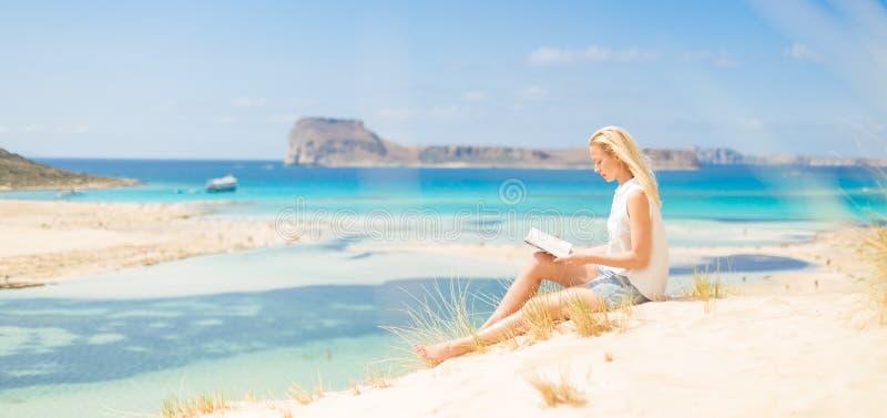 Livro de leitura da mulher, apreciando o sol na praia imagem de stock royalty free