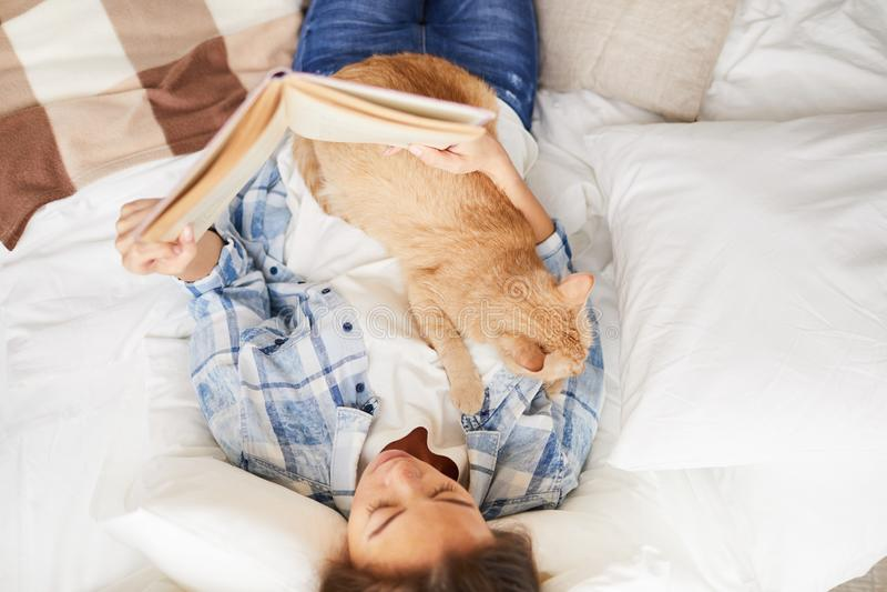 Livro de leitura da mulher com gato foto de stock royalty free