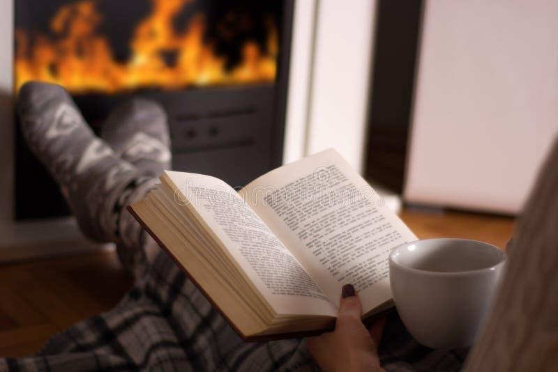 Livro de leitura da mulher e copo da posse dos pés do chá e do aquecimento na frente da chaminé fotos de stock royalty free